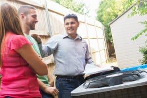 Air conditioner repairman explaining A/C damage to homeowners
