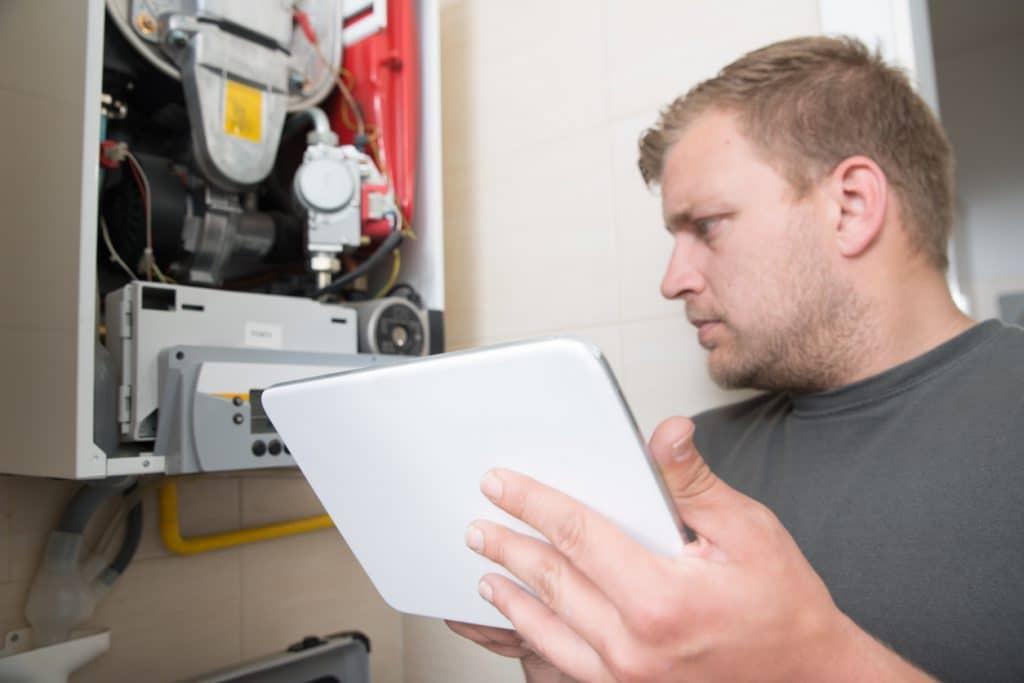 Technician repairing Gas Furnace using digital tablet