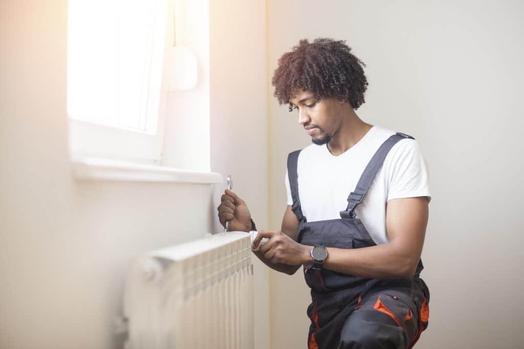 Young man fixing heating