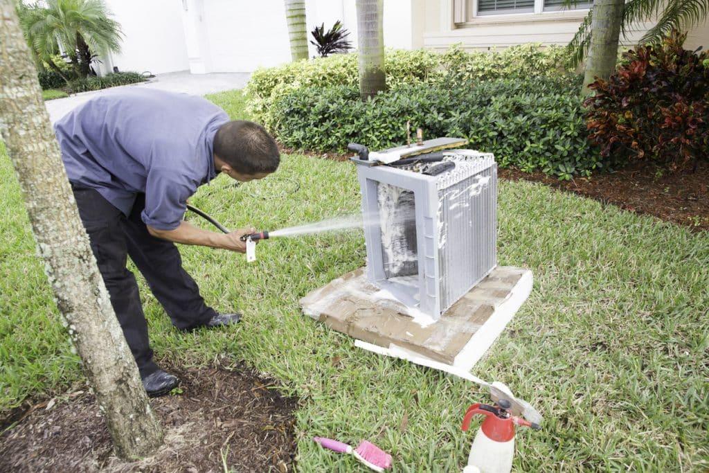 AC repairman acid washing air conditioner coils