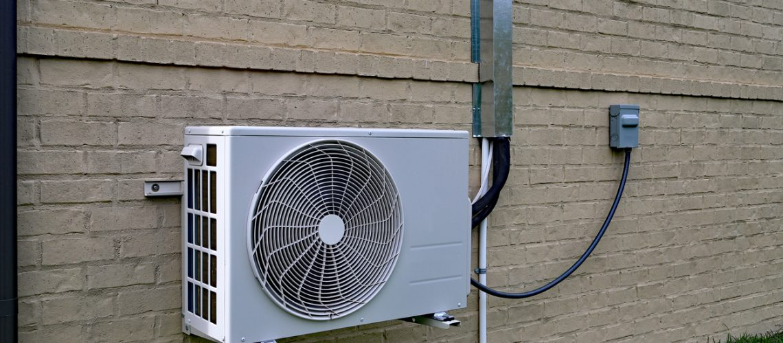 Air Conditioner mini split system next to home with brick wall